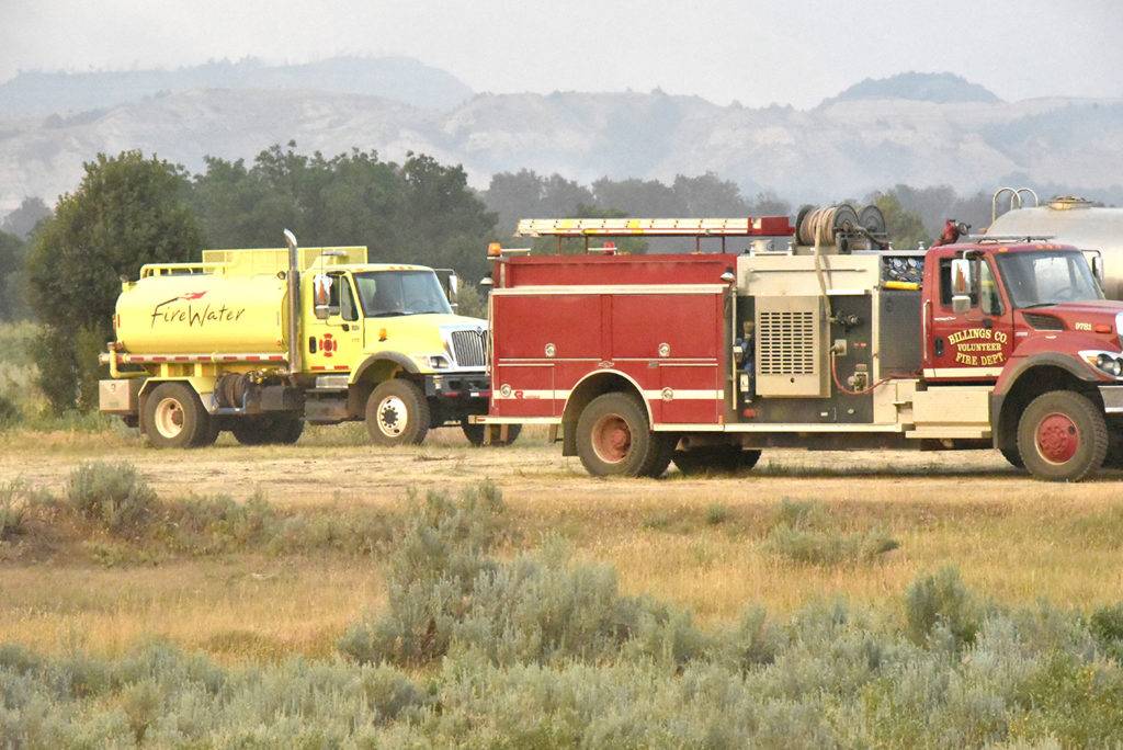 Fire trucks, water trucks and service trucks worked from the staging area west of Magpie Canpground.