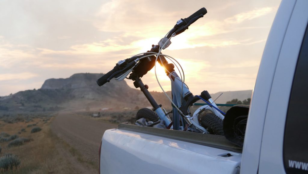 Mountain bike in the bakc of the pickup as the sun sets on the horizon.