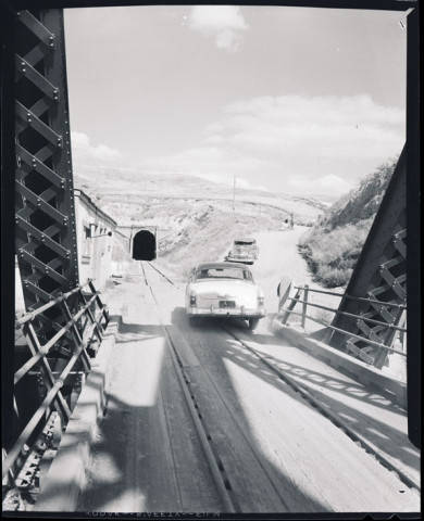 The North Dakota Historical Society holds a collection of images such as this from Bill Shemmory showing a car leaving the bridge headed to the road to the right that would take traffic up over the hill above the railroad bridge.
