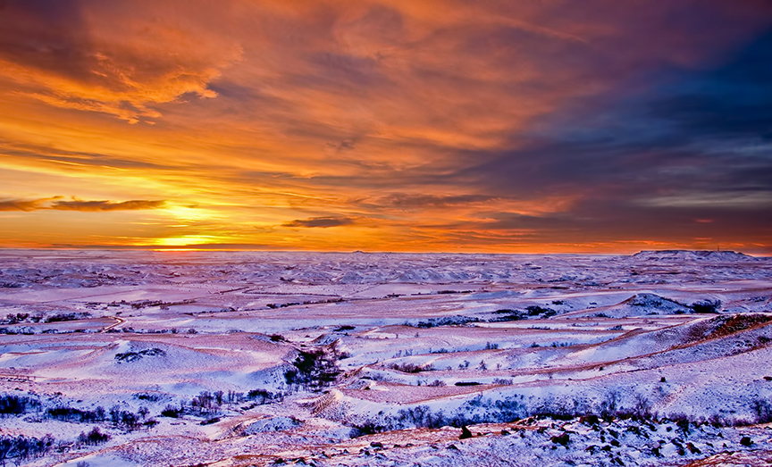 From Square Butte, a blaze orange sunset and cold blue snow, badlands and sentinel butte on the horizon.