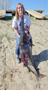 Woman snags paddlefish as big as her!