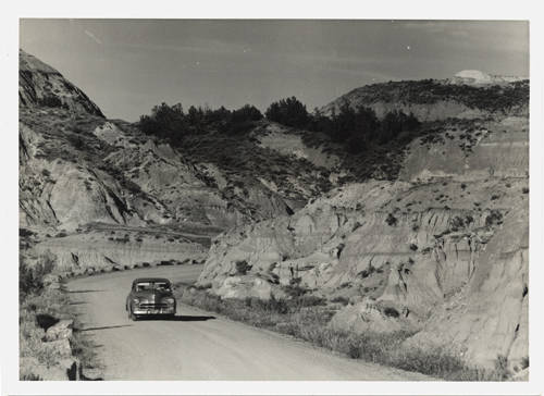 1950's car driving gravel road in Theodore Roosevelt National Memorial Park