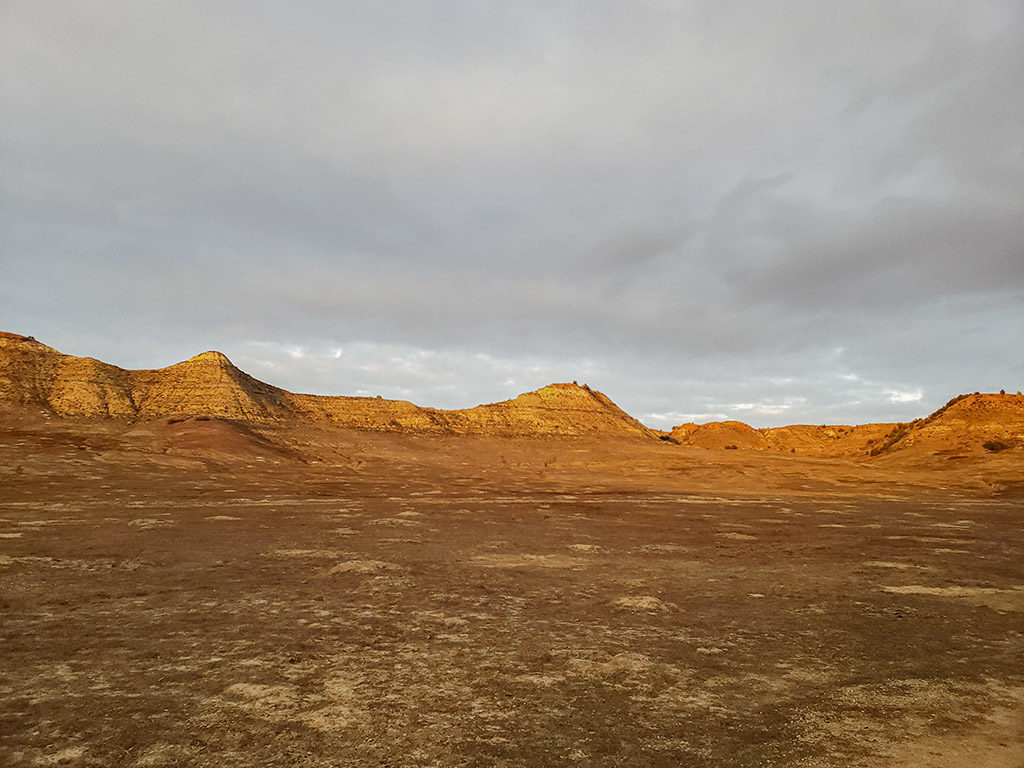 a prairie dog town lays at the base of a ridge of Badlands hills at sunset